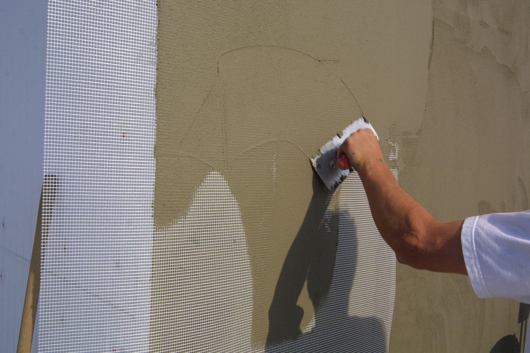 Marouflage de l'armature de verre dans la couche de base puis redoublage